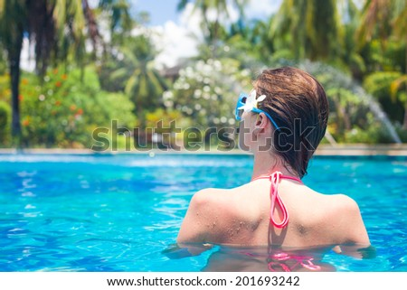 back view of fit woman with flower in hair in luxury spa pool - stock photo