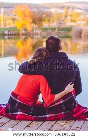 Back view of future parents man and pregnant woman are sitting in warm clothes and blanket infront big lake - stock photo
