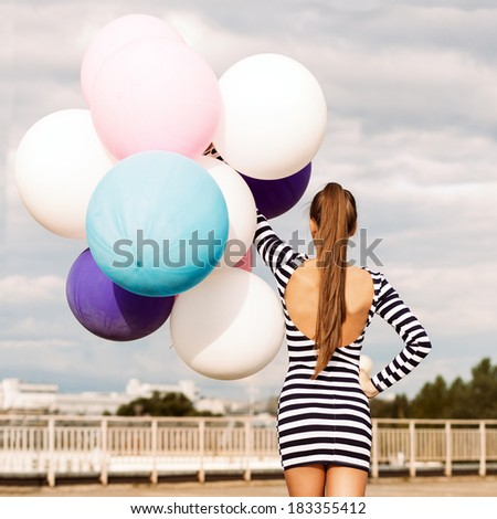 back view of girl in open-back black and white striped short dress and white high top sneakers holds a bunch of multicolored balloons - stock photo