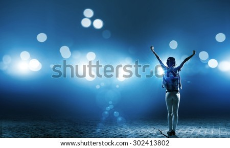Back view of girl standing in stage lights - stock photo