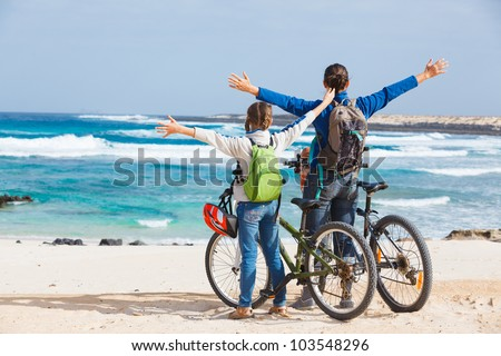 Back view of girl with her mother having a weekend excursion on their bikes on a summer day in beautiful sea landscape - stock photo