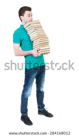 Back view of going  handsome man carries a stack of books. walking young guy . Rear view people collection.  High school student standing with his chin a stack of books. - stock photo