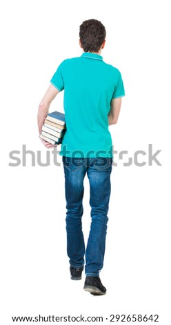 Back view of going  handsome man carries a stack of books. walking young guy . Rear view people collection. Sad man in a green T-shirt goes deep into the frame with a stack of books. - stock photo