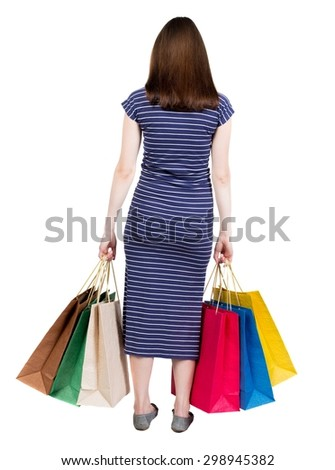 back view of going  woman  in  dress woman with shopping bags . beautiful brunette girl in motion.  Isolated over white background. Girl in a blue striped dress with simplicity colored shopping bags. - stock photo