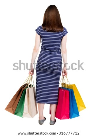 back view of going  woman  in  dress woman with shopping bags . beautiful brunette girl in motion.  backside view of person.. Girl in a blue striped dress with simplicity colored shopping bags. - stock photo
