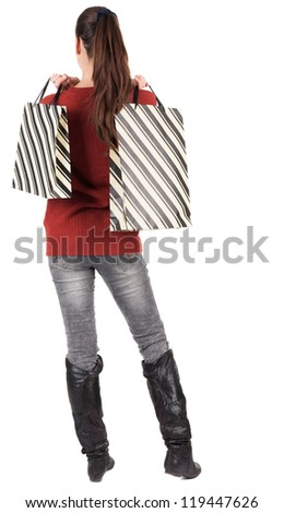 back view of going  woman  in  sweater woman with shopping bags . beautiful brunette girl in motion.  backside view of person.  Rear view people collection. Isolated over white background. - stock photo