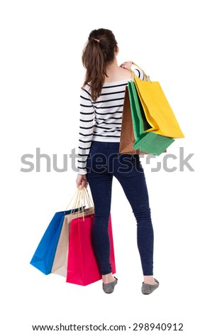 back view of going  woman woman with shopping bags. beautiful brunette girl in motion.  Isolated over white background. Frenchwoman in vest standing with lots of shopping bags. - stock photo