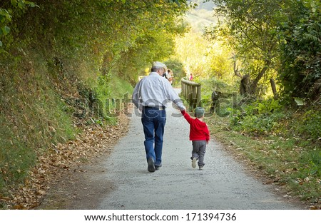 Back view of grandfather and grandchild walking in a nature path - stock photo