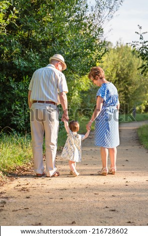 Back view of grandparents and baby grandchild walking on a nature path - stock photo