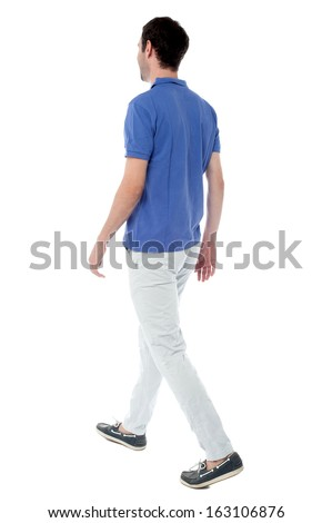 Back view of handsome guy walking in studio - stock photo
