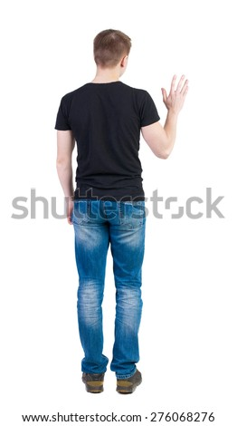 Back view of handsome man in t-shirt  greeting waving from his hands. Standing young guy in jeans. backside view of person.  Isolated over white background. guy in a vest waving uncertainly. - stock photo