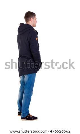 Back view of handsome man in winter jacket looking up. Standing young guy in parka. Isolated over white background. Man in warm jacket is left side with his hands in his pockets.