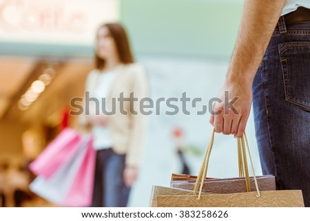 Back view of handsome man meeting his beautiful woman in mall. Both holding shopping bags. Focus on man, close-up - stock photo