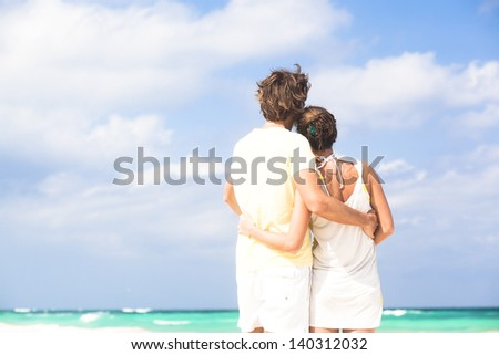 back view of happy couple having fun on the beach - stock photo
