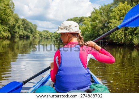 Back view of happy cute girl holding paddle near a kayak on the river, enjoying a lovely summer day