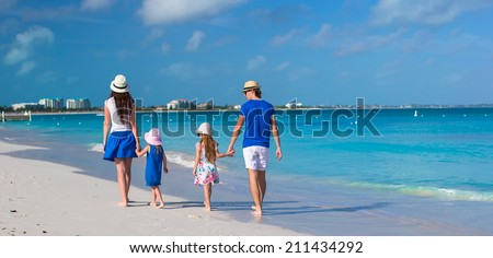 Back view of happy family on tropical beach