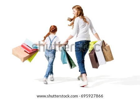 back view of happy mother and daughter holding shopping bags isolated on white