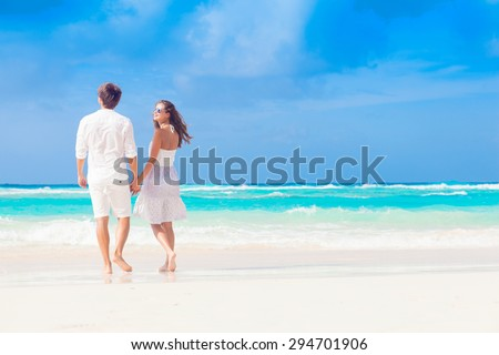 back view of happy romantic young couple walking at the beach - stock photo
