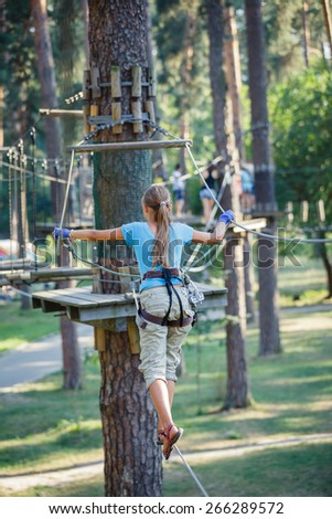 Back view of happy school girl enjoying activity in a climbing adventure park on a summer day - stock photo