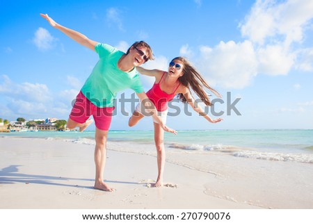 back view of happy young couple on the beach - stock photo