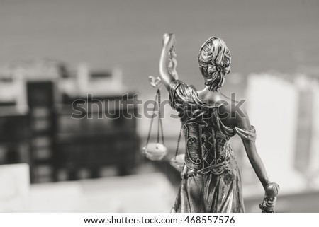 Back view of justice, femida or themis goddess sculpture on light copy space background. Black and white image