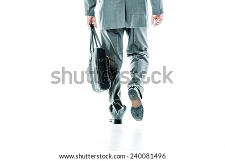 Back view of legs and hands of a businessman carrying a bag isolated on white - stock photo