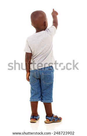 back view of little african boy pointing on white background - stock photo