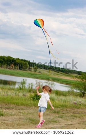 Back view of little girl flying a kite in the countryside - stock photo