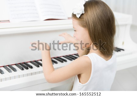 Back view of little girl in white dress playing piano. Concept of music study and art