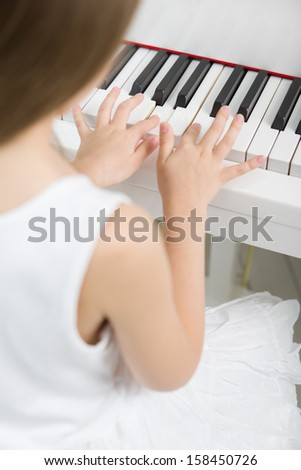 Back view of little girl in white dress playing piano. Concept of music study and arts - stock photo