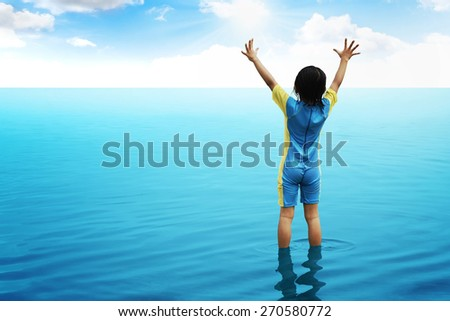 Back view of little girl looking the ocean. Vacation concept image - stock photo
