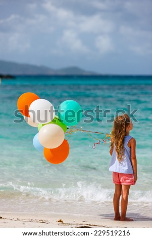 Back view of little girl with colorful balloons at beach during summer vacation - stock photo