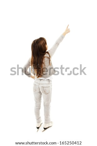 Back view of little girl with ice skates, points at wall. Rear view. Isolated on white background  - stock photo