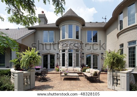 Back view of luxury home with rust colored patio - stock photo