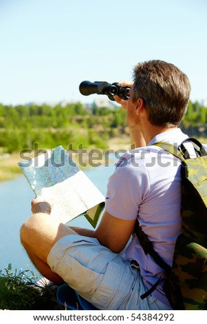 Back view of male tourist looking through binoculars in the country - stock photo