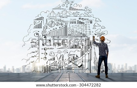 Back view of man engineer drawing plan sketches on wall - stock photo