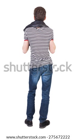 Back view of man in jeans. Standing young guy. Rear view people collection.  backside view of person.  Isolated over white background. Putting his jacket on the shoulders of the guy looks ahead. - stock photo