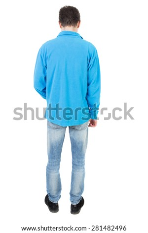 Back view of man in jeans. Standing young guy. Rear view people collection.  backside view of person.  Isolated over white background. The guy in the blue sweater looks down at his feet. - stock photo