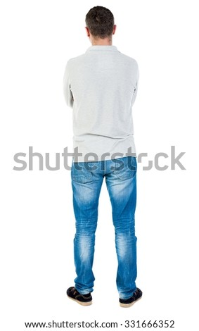 Back view of man in jeans. Standing young guy. Rear view people collection.  backside view of person.  Isolated over white background. A guy in a gray sweater standing with his arms crossed. - stock photo
