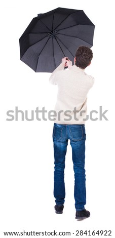 Back view of man in jeans under an umbrella. Standing young guy. Rear view people collection.  backside view of person.  Isolated over white background. guy is trying to keep wind break-out umbrella - stock photo