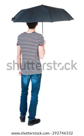 Back view of man in jeans under an umbrella. Standing young guy. Rear view people collection. Isolated over white background. The guy in the striped shirt hiding under an umbrella from the rain. - stock photo