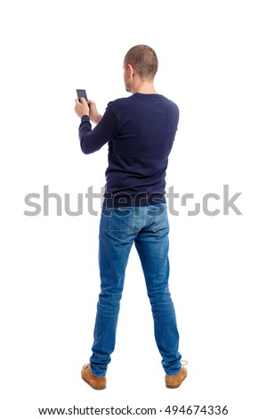 back view of man in suit  talking on mobile phone.    rear view people collection. Isolated over white background. backside view of person. Man in black warm sweater keeps both hands free.