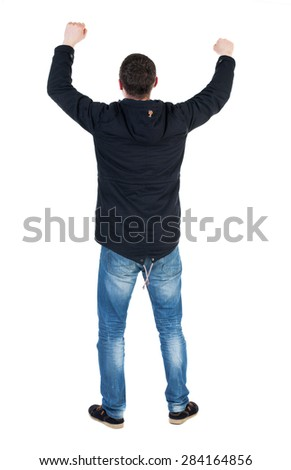 Back view of  man.  Raised his fist up in victory sign.   Rear view people collection.  backside view of person.   A guy in a black jacket with a hood over his head with his fists waving - stock photo