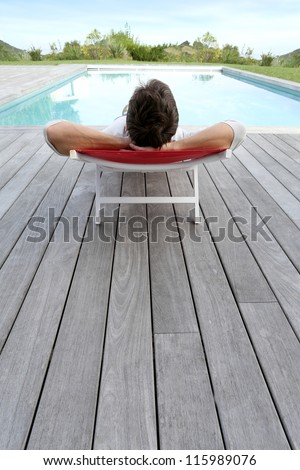 Back view of man relaxing in long chair - stock photo