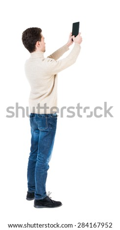 Back view of man with tablet. Standing young guy. Rear view people collection.  backside view person.  Isolated over white background. Curly boy in a white warm sweater tablet takes something in sky - stock photo