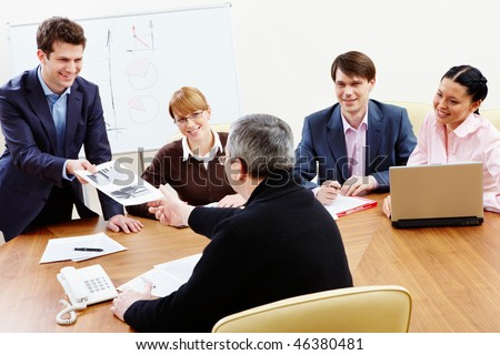 Back view of mature chief passing over paper to employee while the others looking at them - stock photo