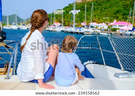 Back view of mother and daughter family sailing on a luxury yacht or catamaran boat - stock photo
