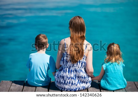 Back view of mother and kids enjoying ocean view - stock photo