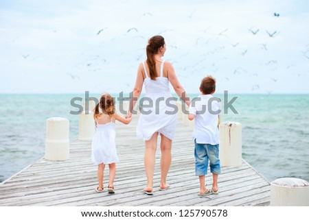 Back view of mother and kids on a wooden dock walking towards hundreds of sea birds