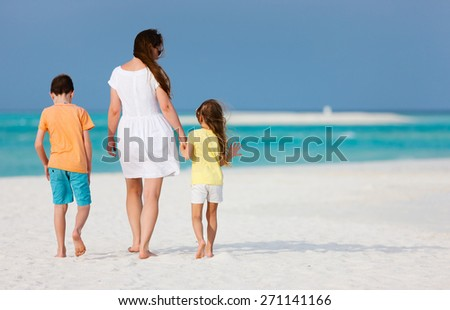 Back view of mother and two kids walking on a tropical beach enjoying summer vacation